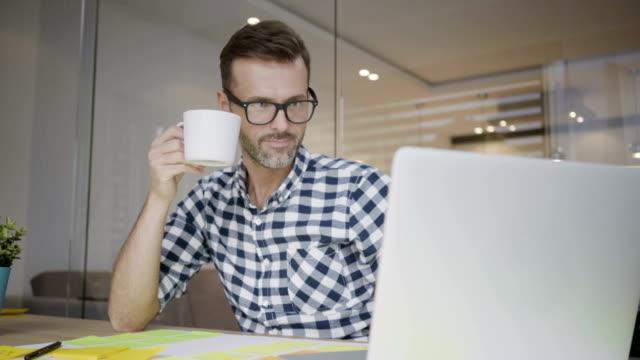 snygg manlig designer som arbetar på laptop och dricka kaffe i hemmakontor - man architect computer bildbanksvideor och videomaterial från bakom kulisserna