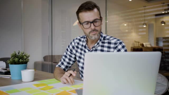 snygg manlig utvecklare som arbetar med laptop och anteckningar och sedan dricka kaffe - man architect computer bildbanksvideor och videomaterial från bakom kulisserna