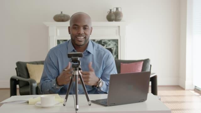handsome man african-american vlogger recording a show - influencer filmów i materiałów b-roll