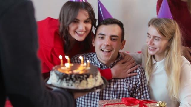 親しい友人のサプライズ ・ パーティー、居心地の良いモダンなアパートでスローモーションを投げながら誕生日の蝋燭を吹くハンサムな男 ビデオ