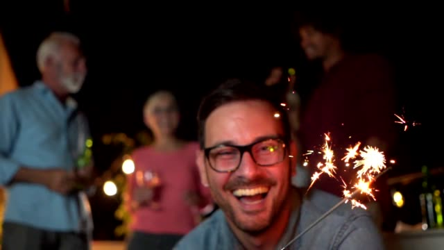 vídeos de stock e filmes b-roll de handsome man celebrating a new year with friends and family - new year