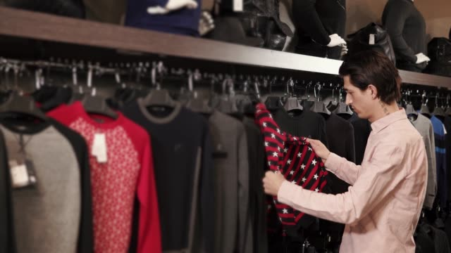 Handsome man choosing clothes video