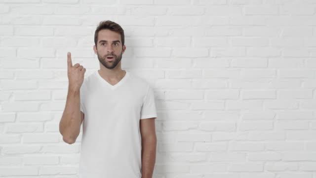 stockvideo's en b-roll-footage met knappe man tellen op vingers - t shirt