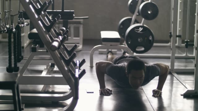 Handsome man doing push-ups working out at fitness club Handhels shot of asian young man doing push-ups at the gym, Bangkok Thailand, 4K Resolution bodyweight training stock videos & royalty-free footage