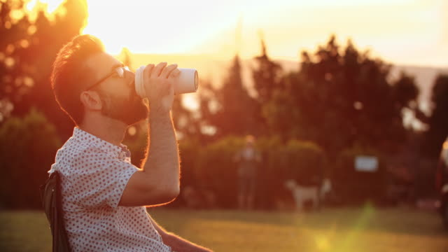 Handsome man drinking coffee in public park at sunset Handsome man drinking coffee in public park at sunset travel stock videos & royalty-free footage
