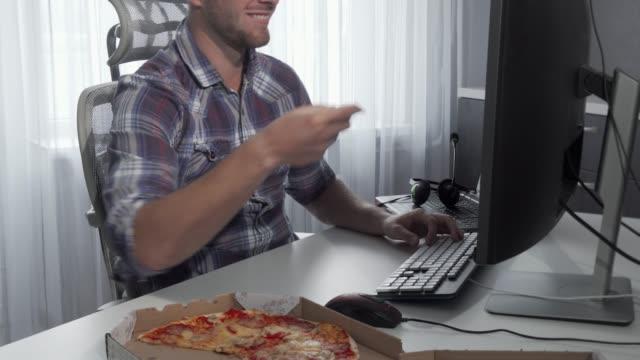 コンピュータで作業しながらおいしいピザを楽しむハンサムな男 - 不健康な食事点の映像素材/bロール
