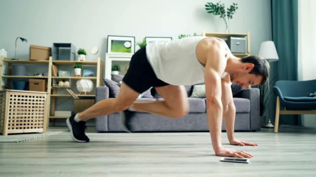 vídeos de stock e filmes b-roll de handsome man exercising at home doing cardio exercise in plank using smartphone. - treino em casa