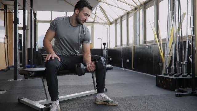 stockvideo's en b-roll-footage met knappe man oefenen met halter in gym - bankdruktoestel