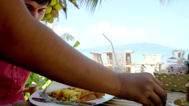 Handsome man gets her order and having breakfast sitting on beach cafe. 3840x2160 video