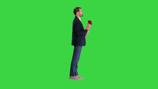 stilig man i kostym som pratar med kameran som håller röda rosor på en grön skärm, chroma key - flörta bildbanksvideor och videomaterial från bakom kulisserna
