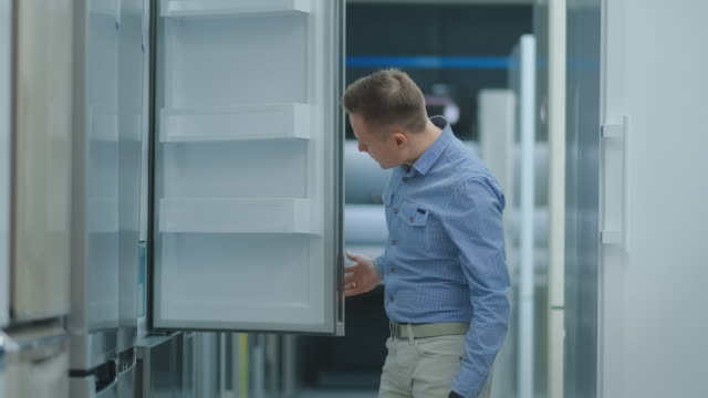 Handsome man in blue shirt open the refrigerator door in appliances store and compare with other models to buy a new home Handsome man in blue shirt open the refrigerator door in appliances store and compare with other models to buy a new home. appliance stock videos & royalty-free footage