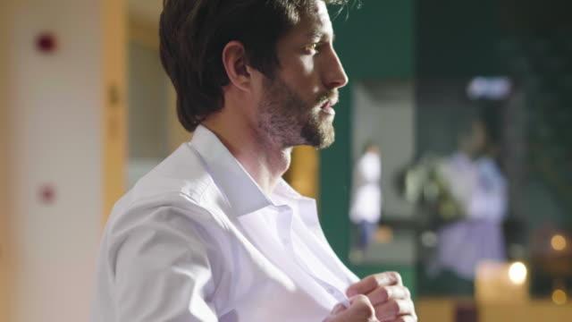 un bell'uomo nel suo loft veste la sua camicia bianca sexy in modo sexy, guarda nella sua stanza e sorride con uno sguardo sicuro a se stesso. - vestirsi video stock e b–roll