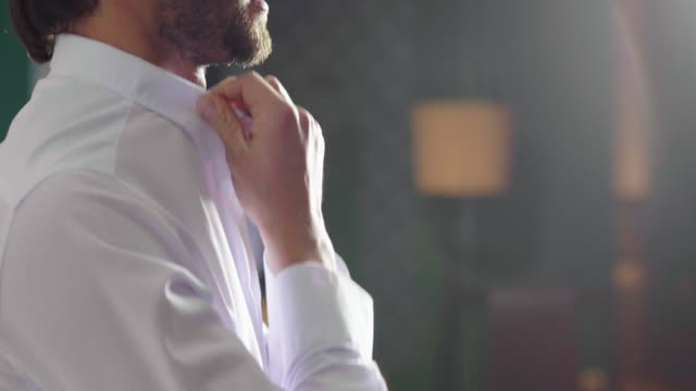 A handsome man in his loft dresses his sexy white shirt in a sexy way, looks into his room and smiles with a sure look at himself. A handsome man in his loft dresses his sexy white shirt in a sexy way, looks into his room and smiles with a sure look at himself. Concept of: elegance, business, work. button down shirt stock videos & royalty-free footage