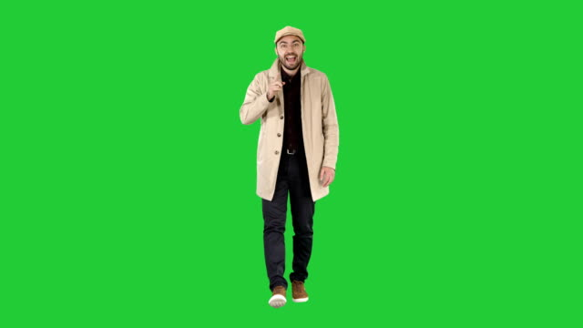 Handsome man in light trench coat talking to camera Focus and think about it gestures on a Green Screen, Chroma Key video