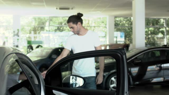 ハンサムな男は、中古車販売店で車を検査し ビデオ