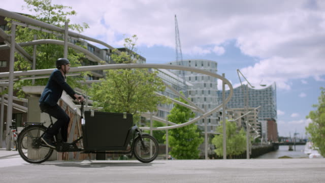 Handsome man is riding with his cargo bike through the city video