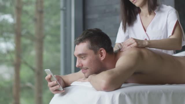 stilig man använder en smartphone under en avkopplande massage i hälsocentret. - massageterapeut bildbanksvideor och videomaterial från bakom kulisserna