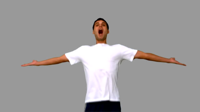stockvideo's en b-roll-footage met handsome man jumping and raising arms on grey screen - t shirt