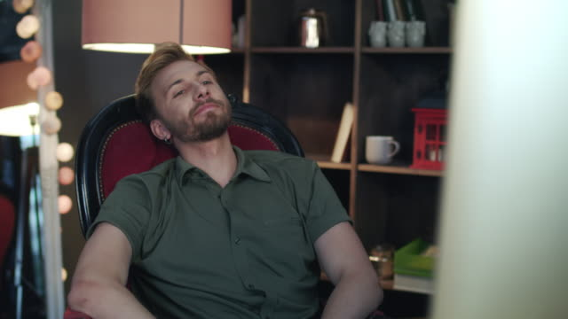 handsome man leaning back from computer. employee falling from broken chair - inarcare la schiena video stock e b–roll