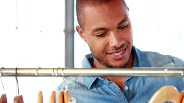 Handsome man looking through clothes rack Handsome man looking through clothes rack in high quality 4k format coathanger stock videos & royalty-free footage