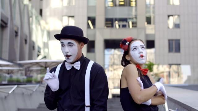 ハンサムな男 mime が彼のガール フレンドに目に見えない花を与える - グリースペイント点の映像素材/bロール