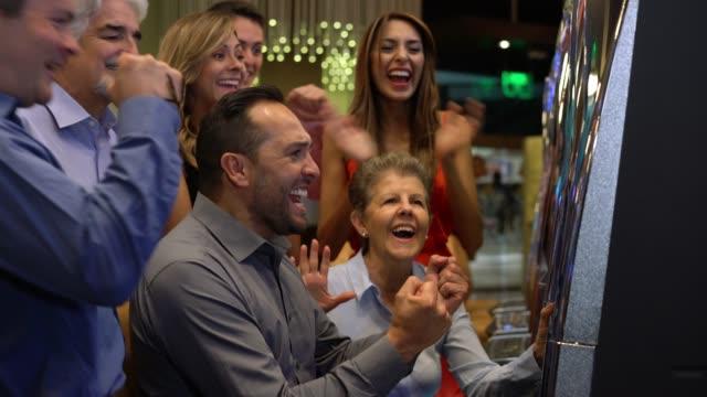 vidéos et rushes de bel homme sur une grève chanceuse à la machine à sous et les personnes célébrant autour de lui - bonne chance