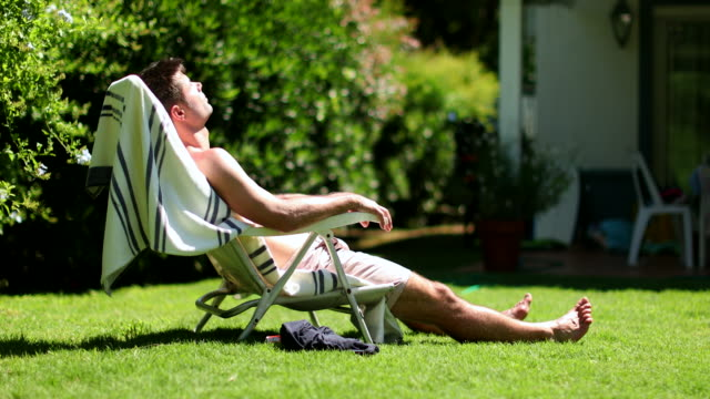 Handsome man outside in backyard sunbathing. Person relaxing during summer vacation Handsome man outside in backyard sunbathing. Person relaxing during summer vacation sunbathing stock videos & royalty-free footage