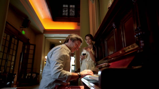Handsome man playing a piano for his wife at a restaurant