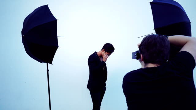 Handsome man posing for camera Photographer taking picture of males model on white background. photo shoot stock videos & royalty-free footage