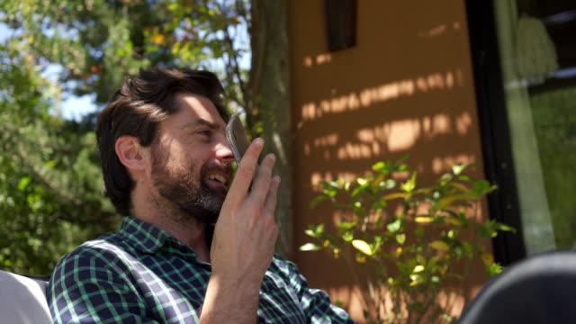 携帯電話でボイスメールを録音するハンサムな男 ビデオ