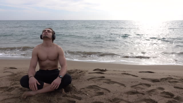Handsome  man resting alone at the beach video