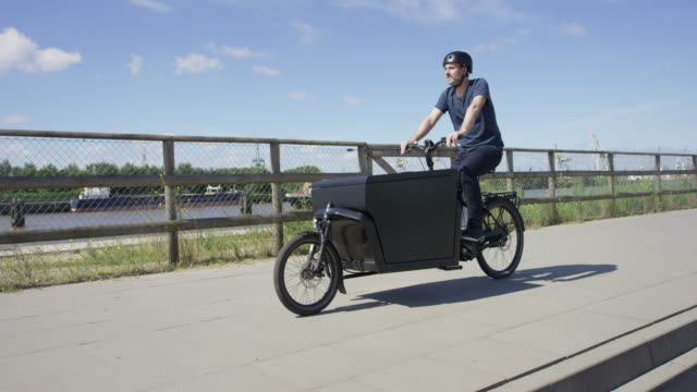 Handsome man riding on black cargo bicycle along a river video