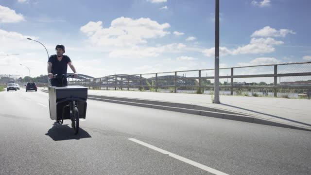 Handsome man riding on black cargo bike along river elbe video