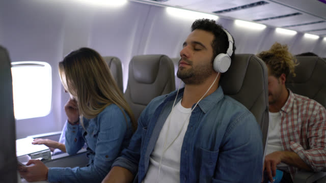 handsome man selecting a playlist and putting on his headphones closing his eyes looking relaxed during air flight - pasażer filmów i materiałów b-roll