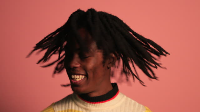 Handsome Man Shaking Dreadlocks Portrait of a man shaking his head in front of a pink background, he is wearing a striped colourful jumper, he is enjoying himself and expressing his freedom. background color stock videos & royalty-free footage