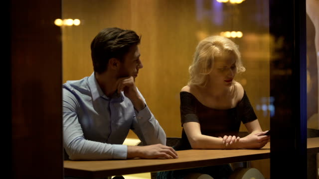 Handsome man sitting in restaurant and flirting with blond woman, relationship video