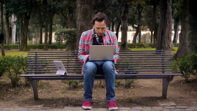 Handsome man sitting on a bench typing on  laptop and using tablet video