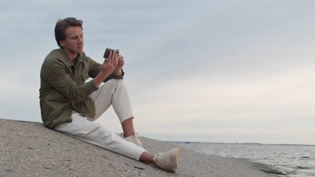 海の海岸に座っているハンサムな男 - 川岸点の映像素材/bロール