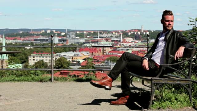 bell'uomo seduto all'aperto - distrarre lo sguardo video stock e b–roll