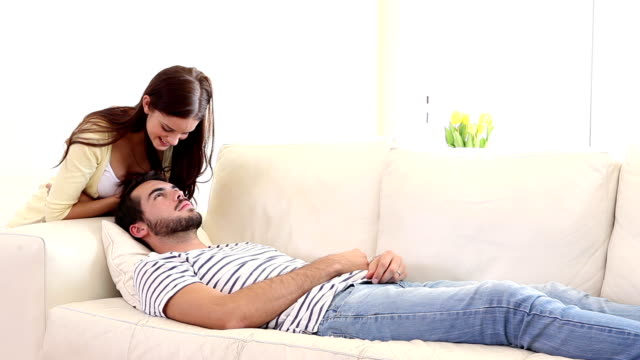 Handsome man sleeping on couch being woken by girlfriend Handsome man sleeping on couch being woken by girlfriend at home in the living room girlfriend stock videos & royalty-free footage