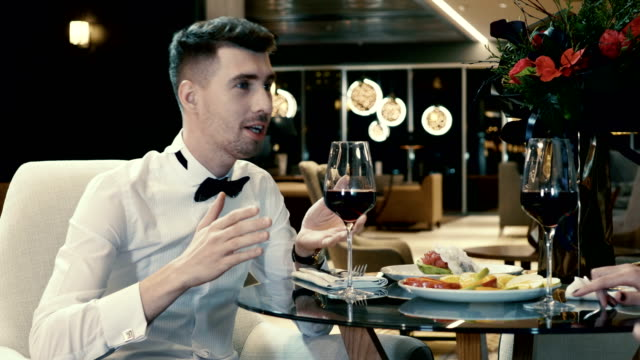 Handsome man smiling, talking with his girlfriend and drinking red wine in restaurant. 4K