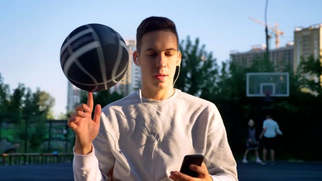 Handsome man spinning basketball on finger and taking selfie or having video chat, wearing earphones, smiling, park in background