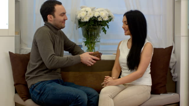 Handsome man surprising his girlfriend with a gift at home in the living room video