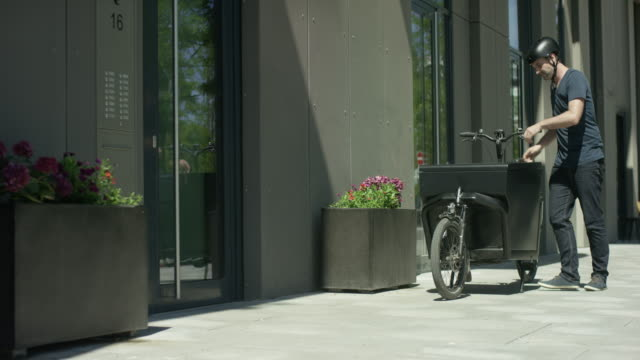 Handsome man takes out a case of his cargo bike and rings a door bell video