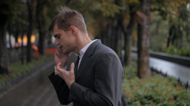 Handsome Man talking on a mobile cell phone. Slow motion. Portrait of young successful confident businessman in the city. Man in a business suit in the autumn street video