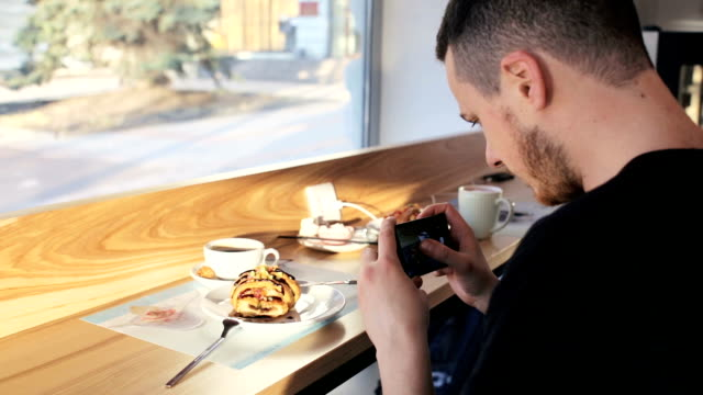 handsome man talking photo of meal with cellphone sitting in cafe - solo un uomo giovane video stock e b–roll