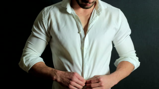 Handsome man unbuttoning his shirt Handsome businessman unbuttoning his shirt button down shirt stock videos & royalty-free footage