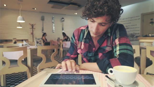 stockvideo's en b-roll-footage met knappe man met behulp van digitale tablet in een koffieshop. - ver