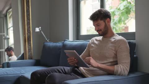 gut aussehender mann mit digital-tablette. - junge männer stock-videos und b-roll-filmmaterial