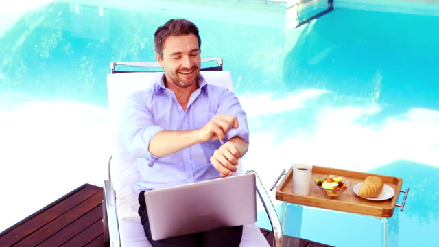Handsome man using laptop on deck chair Handsome man using laptop on deck chair poolside sleeve stock videos & royalty-free footage